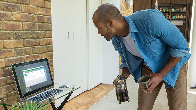 Vīrietis skatās galddatora ekrānā, kas stāv uz stikla galda; viņam rokās ir kafijas preskanna un krūze