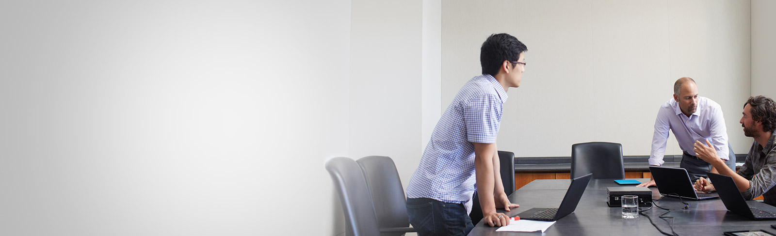 Tiga orang lelaki dengan komputer riba bermesyuarat di bilik persidangan menggunakan Office 365 Enterprise E4.