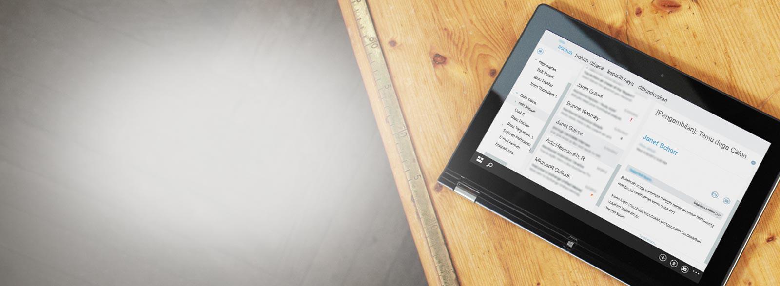 Tablet di atas meja, menunjukkan tangkapan dekat peti masuk e-mel perniagaan, dikuasai oleh Exchange.