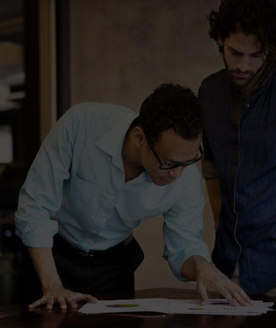Dua lelaki bekerja di dalam pejabat menggunakan Office 365 Enterprise E4.