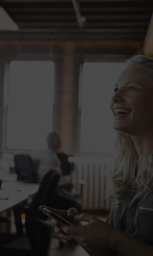 Seorang wanita di dalam pejabat, menggunakan Office 365 Business Essentials pada telefon pintar.