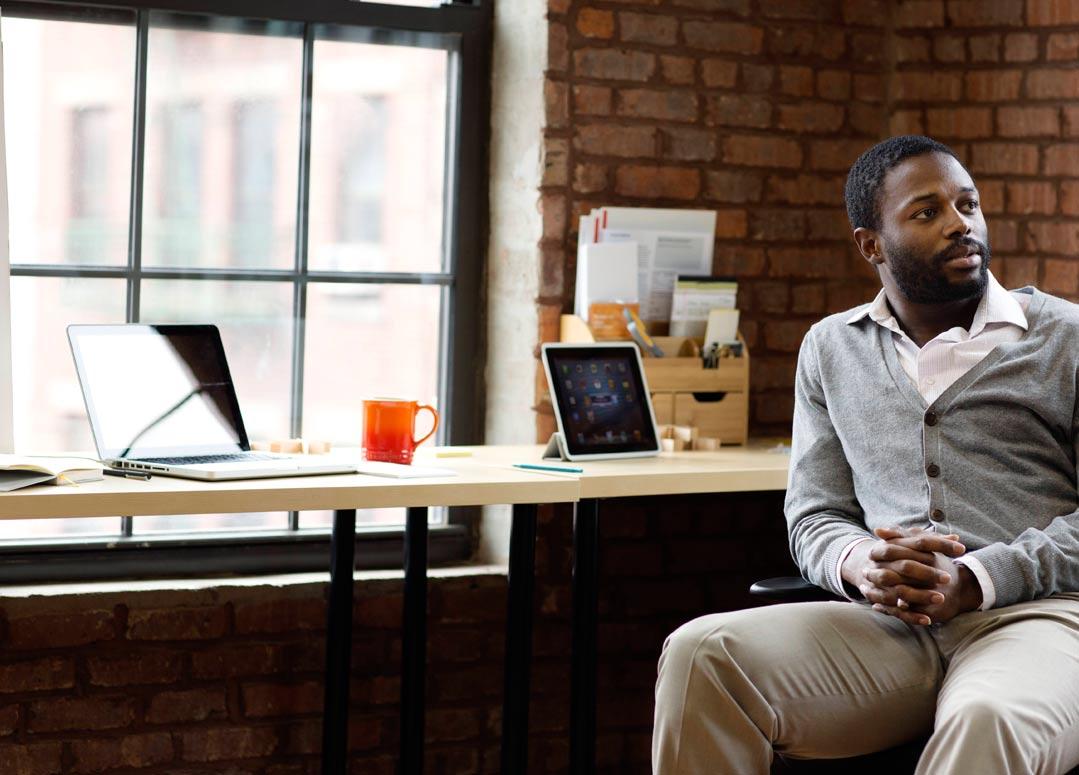 Seorang lelaki duduk di tepi meja dengan tablet dan komputer riba menggunakan Office 365 Business Premium.
