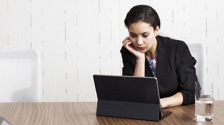 Seorang wanita duduk di meja, bekerja menggunakan komputer tablet