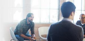 Tiga orang lelaki dalam mesyuarat. Office 365 Enterprise E1 meringkaskan aktiviti kerjasama.