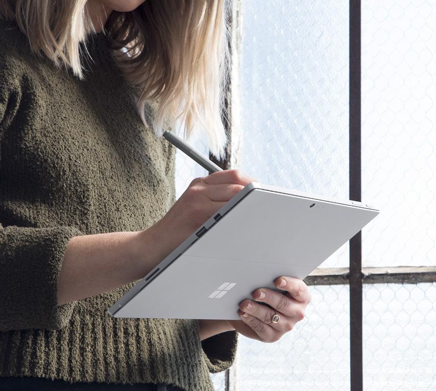 Wanita menggunakan Surface Pro dalam mod papan klip.