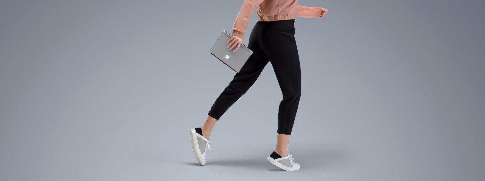 Surface Go dipegang oleh perempuan yang sedang berjalan