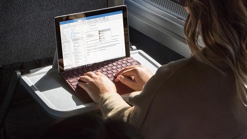Seorang wanita membuat kerja menggunakan Surface Go dengan Surface Go Signature Type Cover dalam kereta api