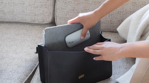 Seorang wanita memasukkan Surface Go dan Surface Mobile Mouse dalam beg duit beliau