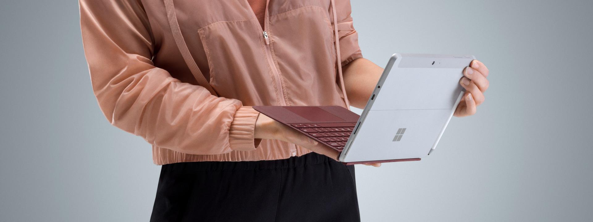 Seorang perempuan berjaket merah jambu memegang Surface Go
