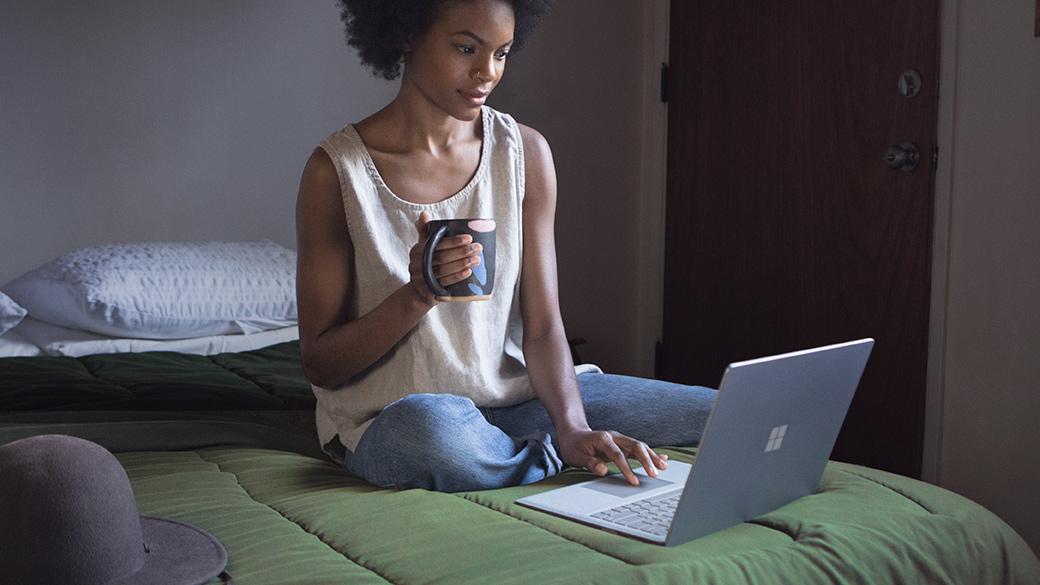 Wanita di atas katil dan bekerja menggunakan Surface Laptop.