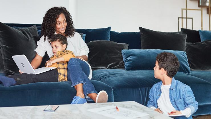En mor sitter i sofaen med barn og bærbar PC med Windows 10