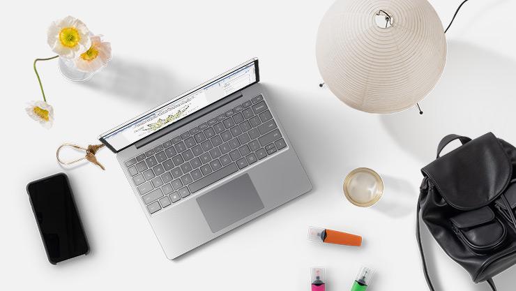 Bærbar PC med Windows10 på et skrivebord ved siden av telefon, håndveske, blomster, merkepenner, drikke og lampe.