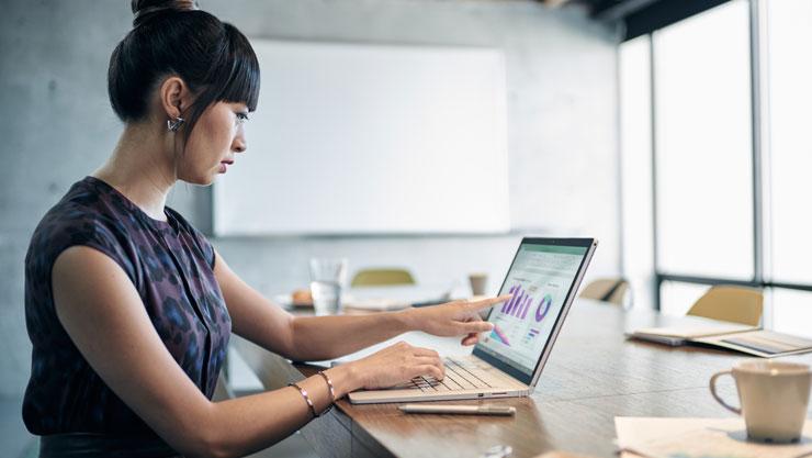 Kvinne som sitter ved et bord på en kafé og bruker Surface Book 2, berører skjermen.