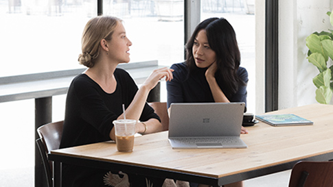 To kvinner sitter på en kafé med en Surface Book 2 i visningsmodus foran seg.