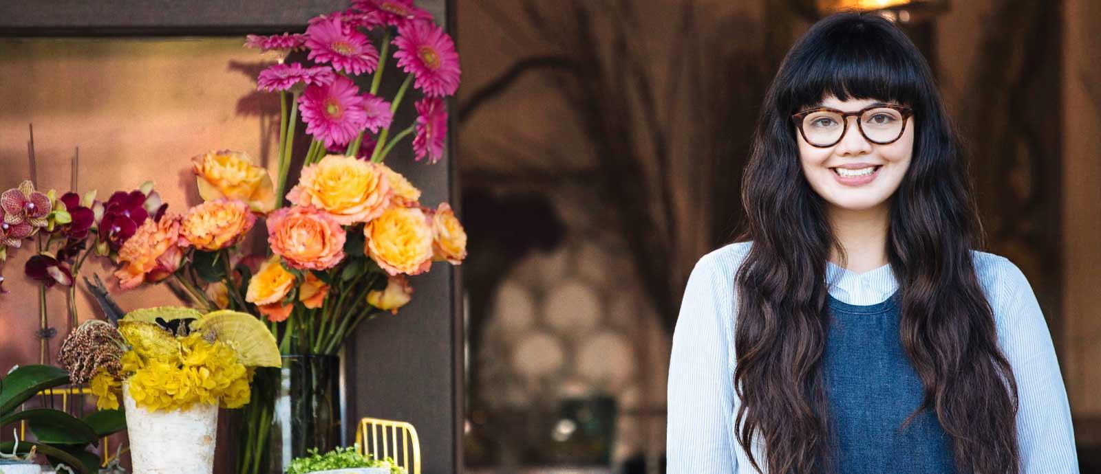 En smilende ung kvinne med briller som står utendørs med blomster i bakgrunnen.