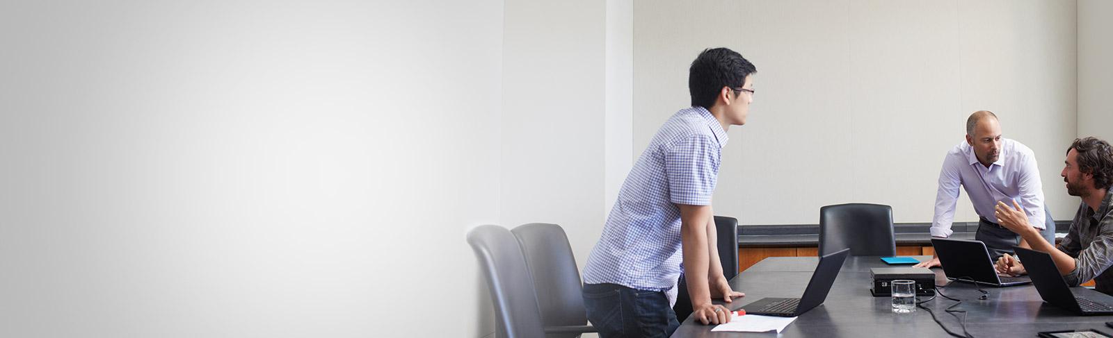 Tre menn med bærbare datamaskiner som møtes i et konferanserom og bruker Office 365 Enterprise E4.