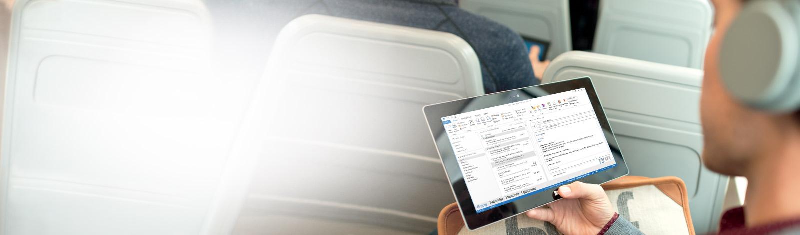 En mann holder et nettbrett som viser innboksen hans. Få tilgang til e-post hvor som helst med Office 365.