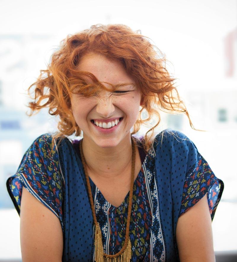 En kvinne som smiler. Med nye Office for Mac kan du få arbeidet gjort hvor som helst.