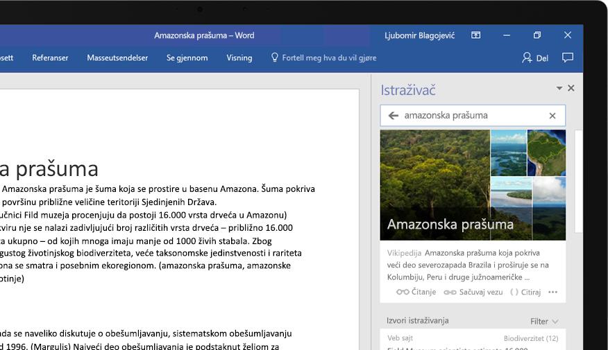 En bærbar datamaskin viser et Word-dokument og et nærbilde av Researcher-funksjonen med en artikkel om Amazon-regnskogen