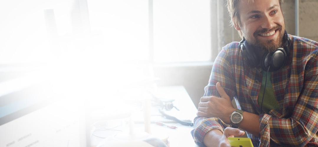 En mann som sitter ved skrivebordet og holder en telefon med Office 365 Enterprise E1.