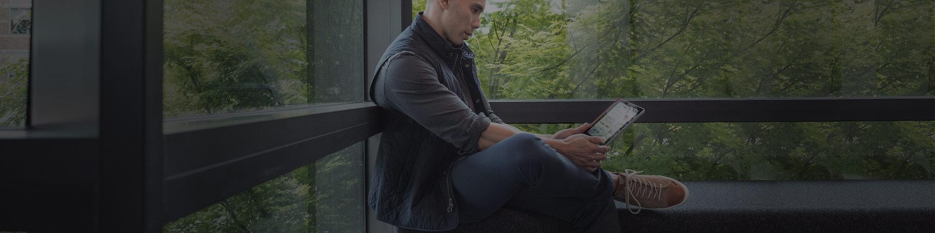 En mann sitter på en benk og ser på en enhet han holder i hendene
