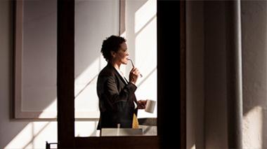En kvinner står ved et vindu, og leser vanlige spørsmål om Visio