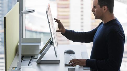 Mann arbeider i Surface Studio ved å bruke berøringsskjerm.