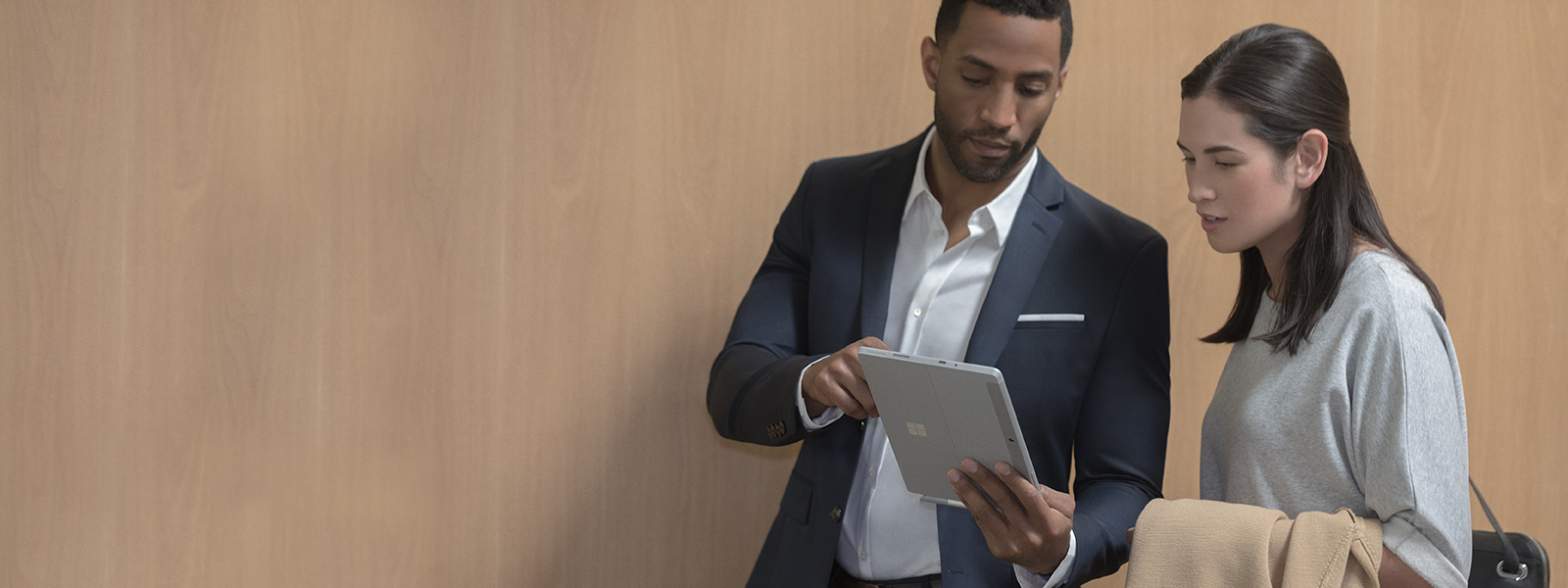 Mann og kvinne går i gangen på kontoret med sølv- og burgunderfargede Surface Go-enheter