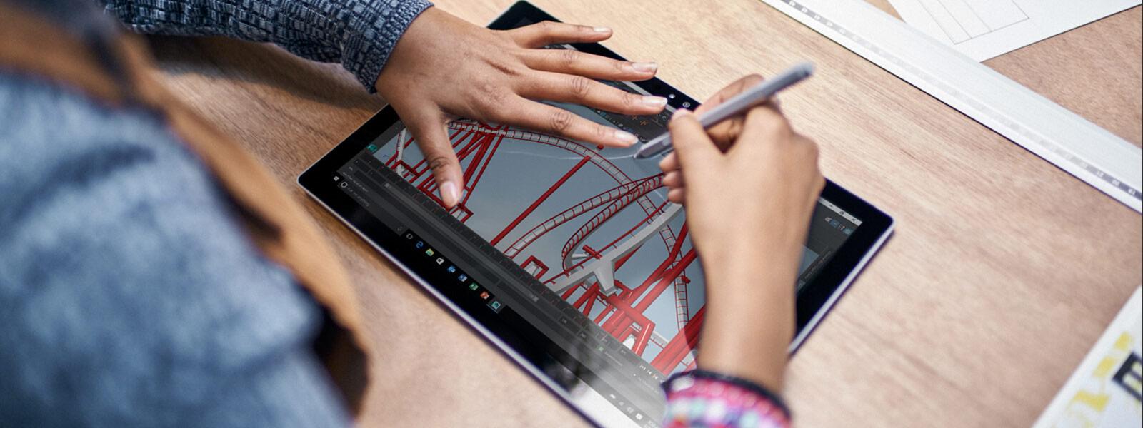 Kvinne tegner på en Surface-skjerm med Surface-pennen.