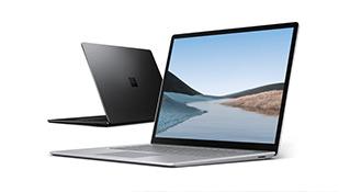 Een zwarte en platina Surface Laptop 3 staan opengeklapt met de rug naar elkaar toe, waarbij de platina Surface Laptop 3 een scherm met heuvels en water toont