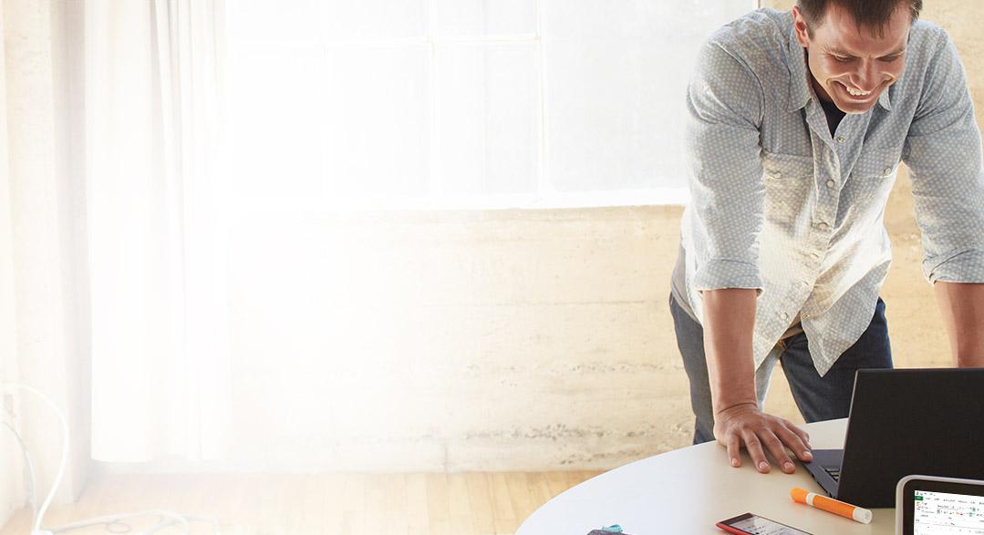 Een man die voorover buigt naar een laptop op een bureau en gebruikmaakt van Office 365 Business Essentials.