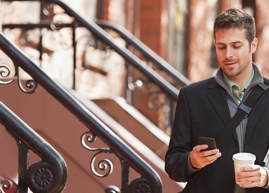 Een man met een smartphone in zijn hand waarop hij Office 365 Enterprise E1 gebruikt.