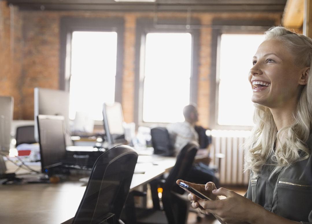 Een vrouw in een kantoor met Office 365 Business Essentials op een smartphone.