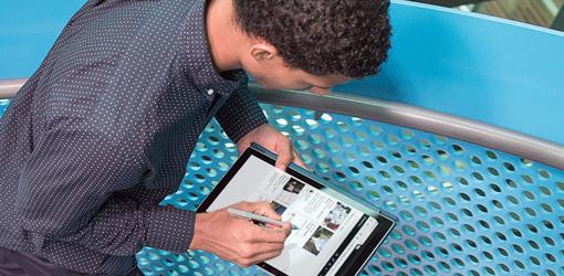 een man die naar een tabletcomputer kijkt waarop SharePoint wordt uitgevoerd