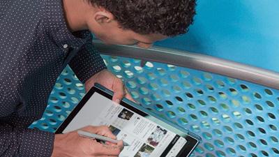 een man die naar een tablet kijkt waarop SharePoint wordt uitgevoerd