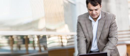 Een staande man die op een laptop typt, informatie over Exchange Online-functies