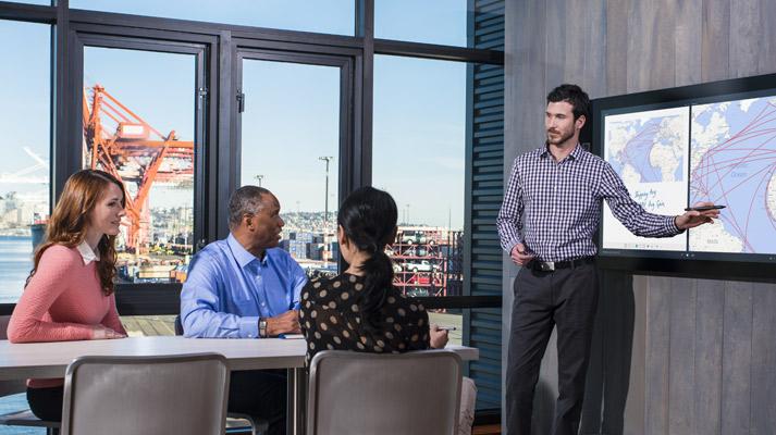 Man die iets aanwijst op een presentatie en twee collega's die geïnteresseerd toekijken.