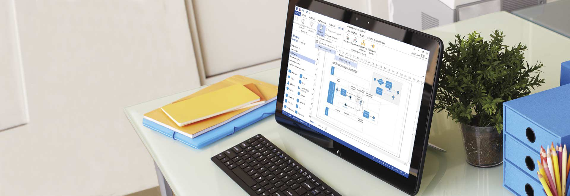 Een bureau met een tabletcomputer waarop een procesdiagram in Visio Professional 2016 wordt weergegeven