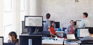 Zes personen praten en werken op hun desktopcomputers met Office 365 Business.