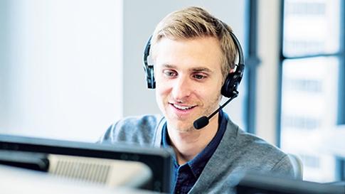 Man met headset typt op een gewone desktopcomputer.