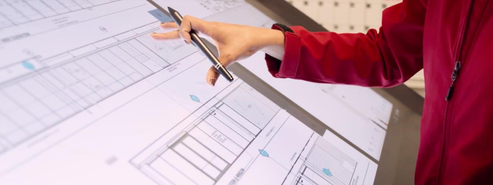 Suffolk Construction-medewerker werkt aan een blauwdruk op een Surface Hub.