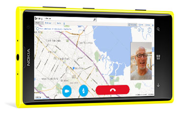 Een smartphone met een kaart en een kleine afbeelding van een deelnemer aan een videovergadering.