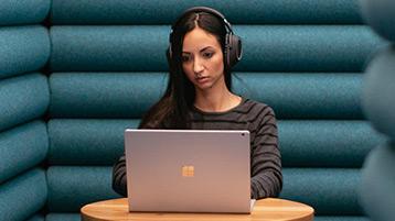 Een vrouw zit rustig alleen met een koptelefoon op terwijl ze op haar Windows10-computer werkt