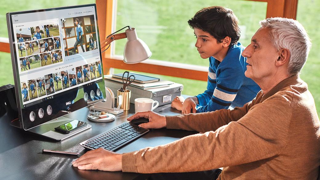 Een man en een jonge jongen zitten aan een bureau op een alles-in-één-computer en verkennen de Foto's-app