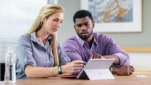 Twee personen typen en kijken naar Surface Pro 4.