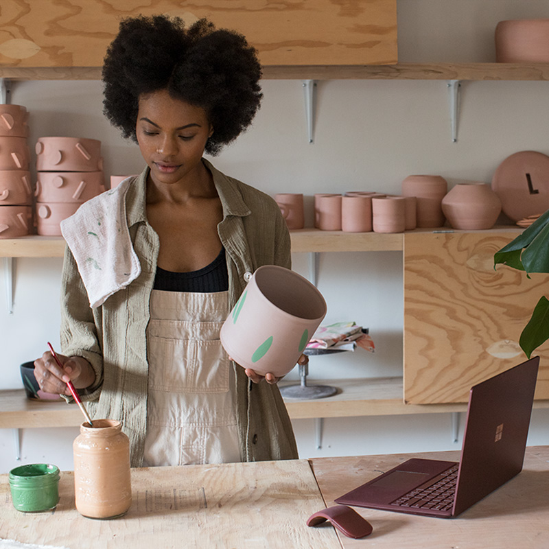 Kenesha Sneed met Surface Laptop en Surface Arc Mouse in haar keramiekatelier.