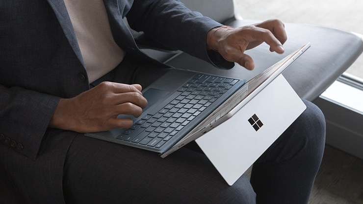 Man typt gezeten op een vliegveld op een kobaltblauwe Surface Pro.
