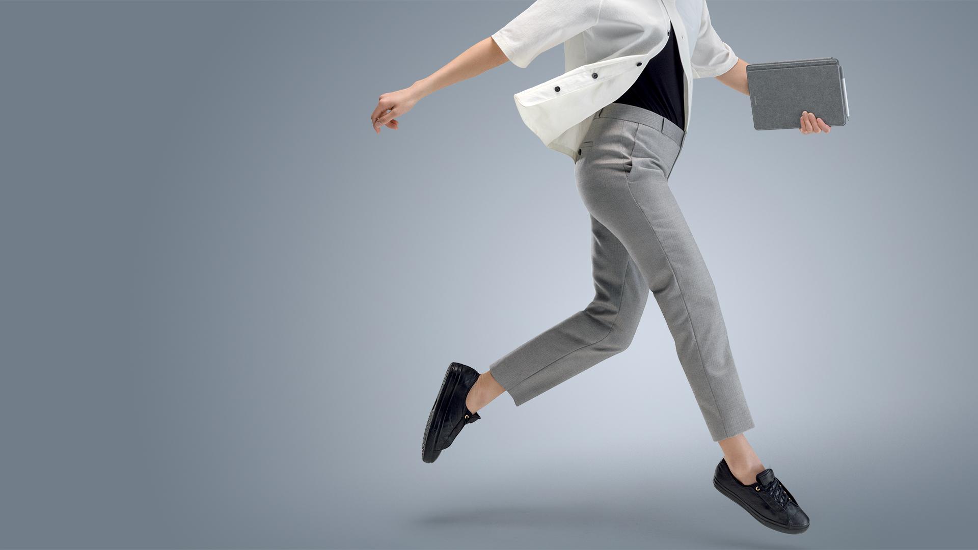 Een vrouw springt terwijl ze Surface Go in tabletmodus in één hand draagt