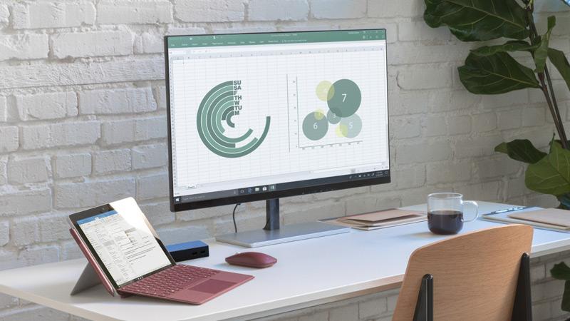 Surface Go is verbonden met het Surface-basisstation, zodat je je werk op externe monitors kunt bekijken voor een volledige werkstationervaring