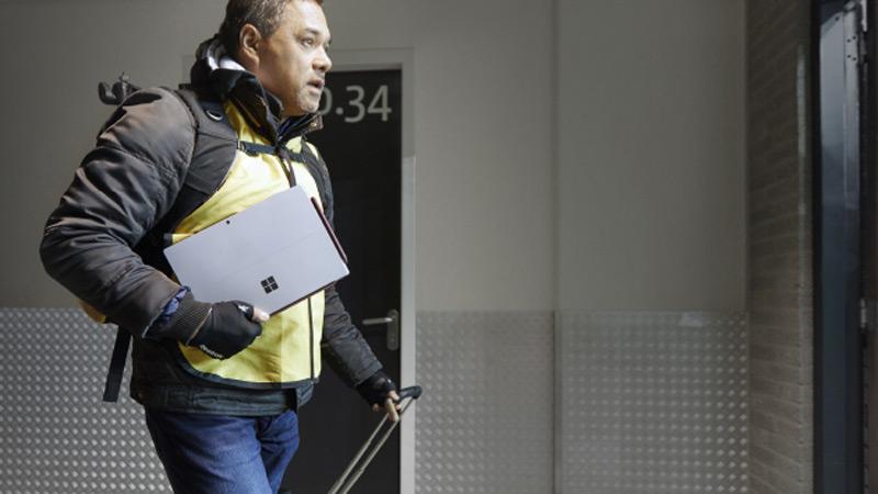 Een lopende man met een Surface Pro in zijn hand.